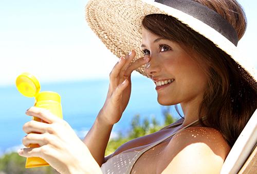 Девушка наносит солнцезащитное средство на лицо