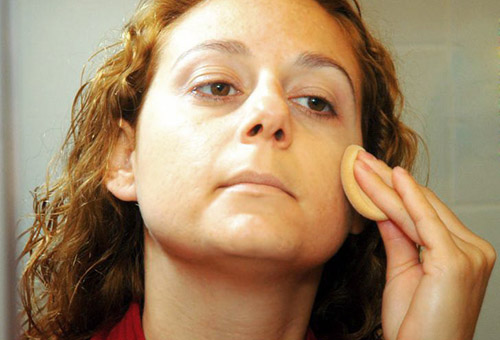 Женщина протирает лицо маслом жожоба