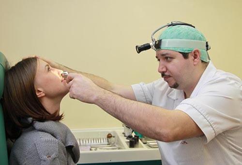 Врач диагностирует фурункул на лице