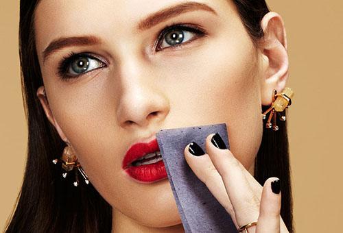 Девушка поправлят макияж матирующими салфетками