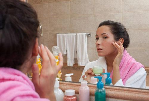девушка перед зеркалом с кремом для лица