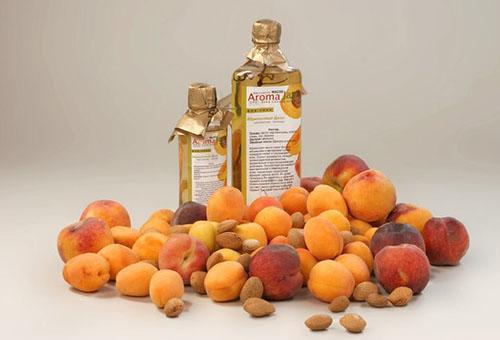 Абрикосовое масло в бутылках и плоды абрикоса