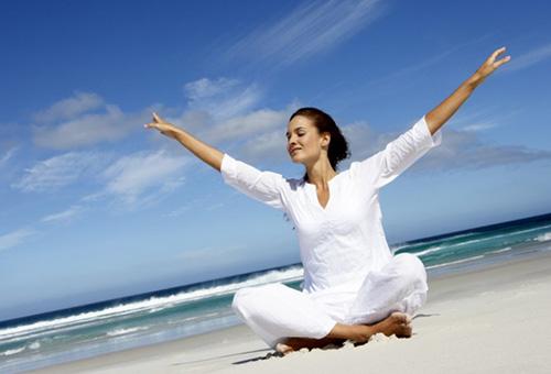 Девушка занимается медитацией на берегу моря