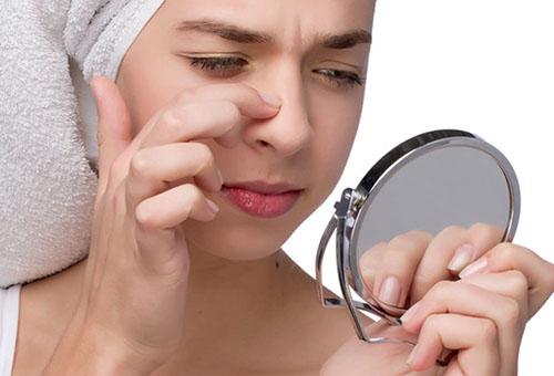 Девушка рассматривает свое лицо в зеркале