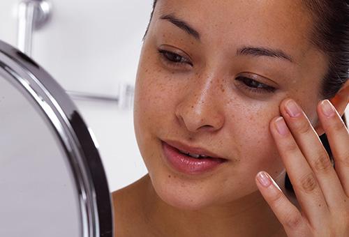 Девушка рассматривает веснушки в зеркале