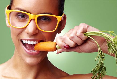 Девушка грызет морковь