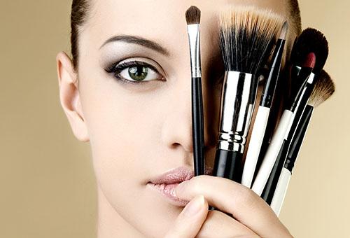 Девушка с макияжем и косметическими кистями