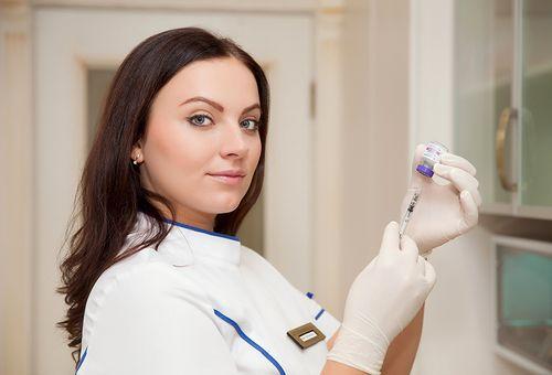 Женщина врач со шприцом в руке